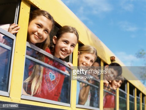 Group of children in a school bus, looking out the window : Stock Photo
