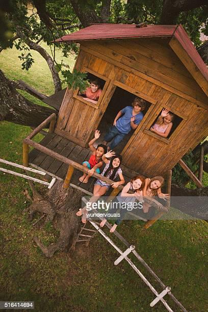 Groupe de enfants Treehouse souriant et en agitant