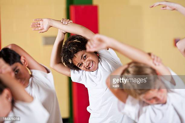 Group of children in phys ed class stretching
