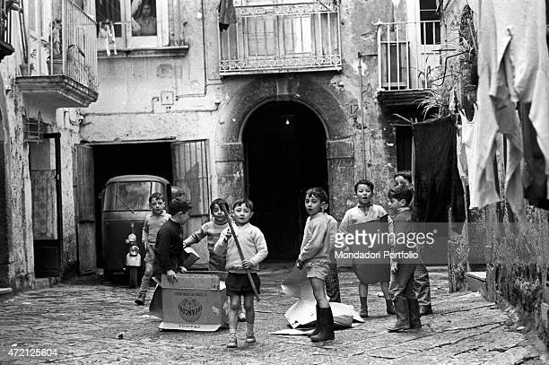 'A group of children is messing with cardboard boxes and pieces of wood about while inventing games in a small courtyard clothes hanging out at the...