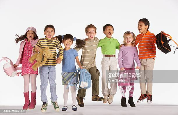 Group of children (6-8), jumping in air, smiling, portrait
