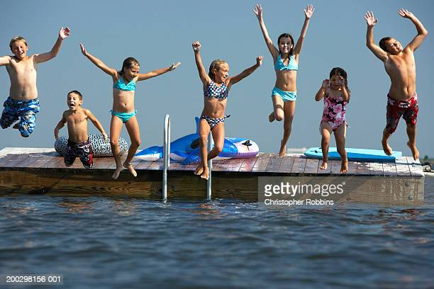 Group of children (5-12) leaping off landing platform into sea