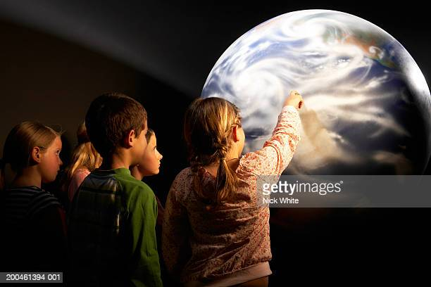 Group of children (8-10) looking at model of Earth, rear view