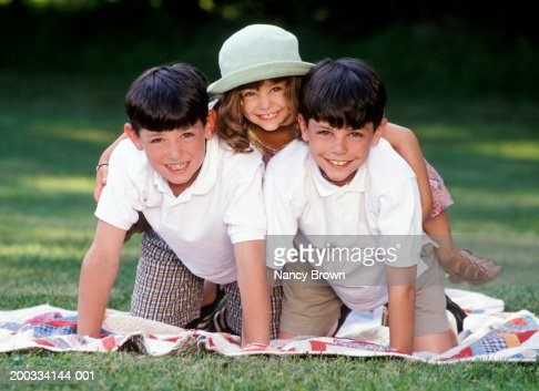Group of children making human pyramid, smiling, portrait, close-up : Stock Photo