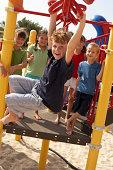 Group of children (6-9) on climbing frame, boy on monkey bars