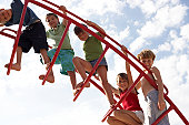 Group of children (6-9) on climbing frame, portrait, low angle view