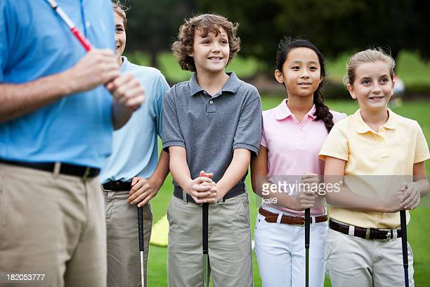 Group of children on golf driving range with instructor