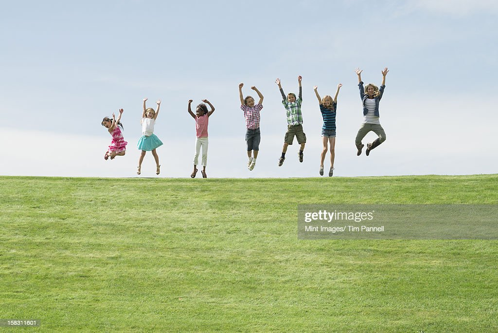 A group of children on the top of a hill, in a row leaping into the air. : Stock Photo