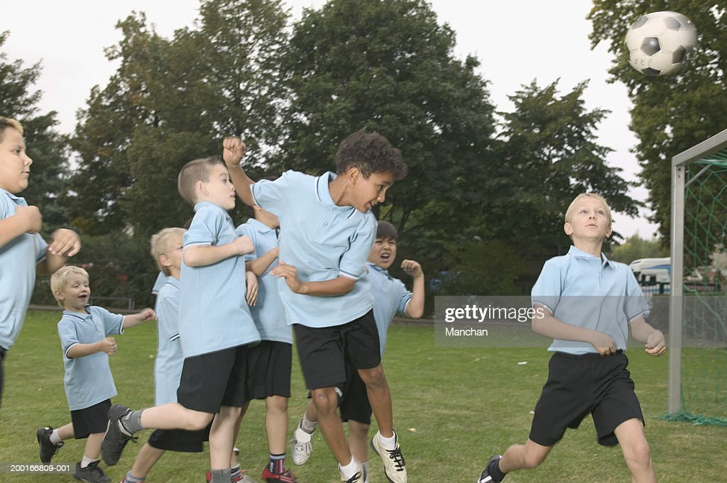 Group of children (5-9) playing football : Stock Photo