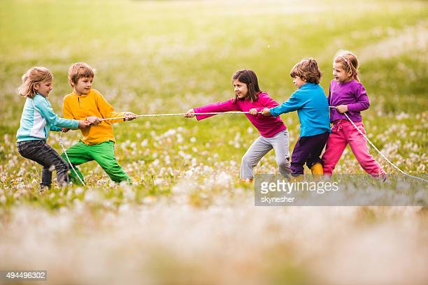Group of children playing tug-of-war in nature.