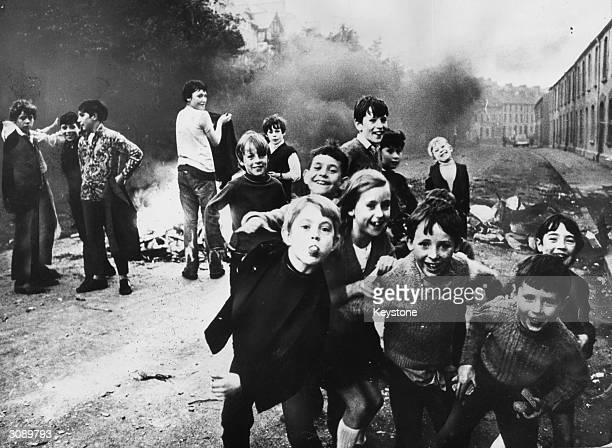 Children jeer at British soldiers whiile a fire smoulders in the street behind them