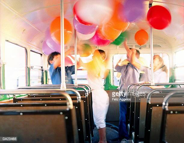 Group of children (6-9) playing with balloons on bus