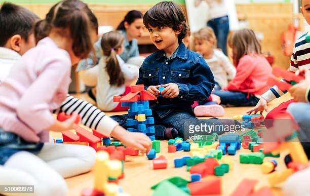 Group of children playing with blocks in kindergarten.