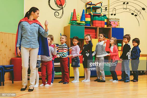 Group of children playing with their teacher in kindergarten