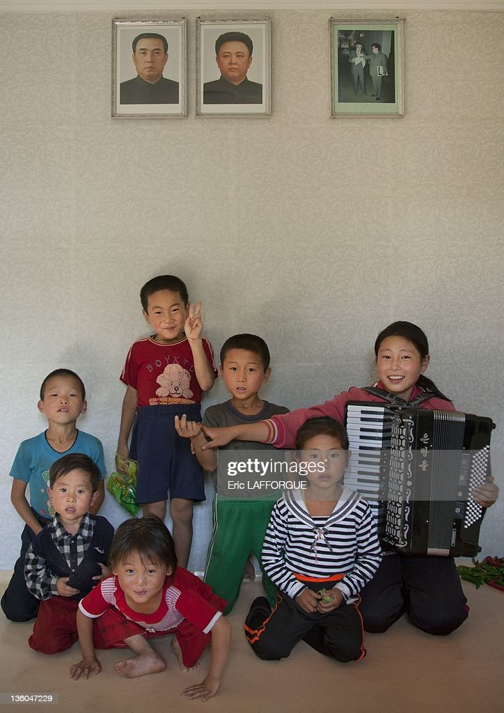 Group of children pose under Kim Jong Il and Kim Il Sung portraits on September 12, 2011 in Pyongyang, North Korea.