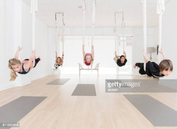 Group of children practicing aerial yoga