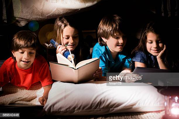 Group of children read together in homemade tent at home.