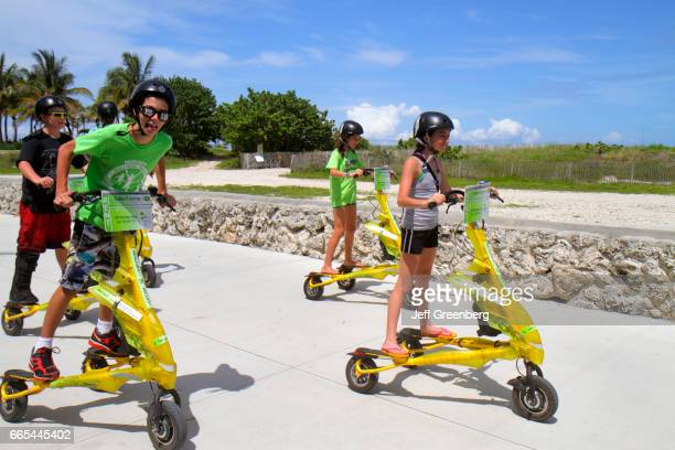 A group of children riding a Tribred by Trikke electric vehicle in Lummus Park