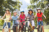 Group Of Children Riding Bikes In Countryside Wearing Cycle Helmets