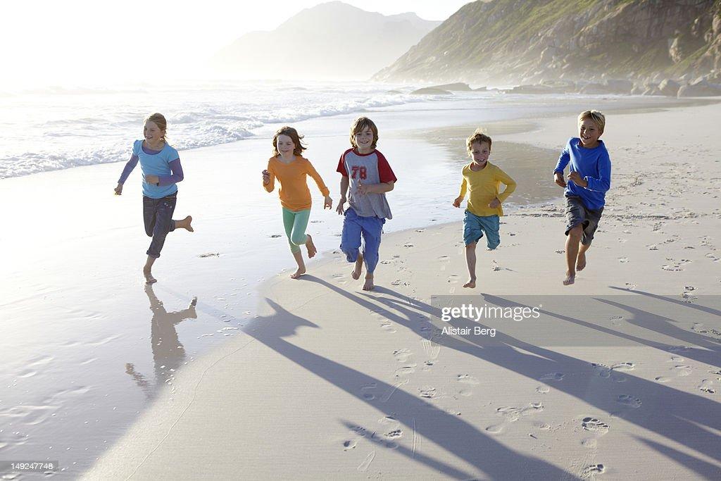 Group of children running along a beach : Stock Photo