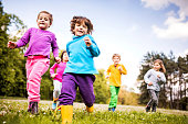 Group of children running in nature.