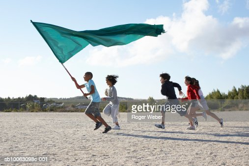 Group of children (9-12) running on beach with flag : Stock Photo