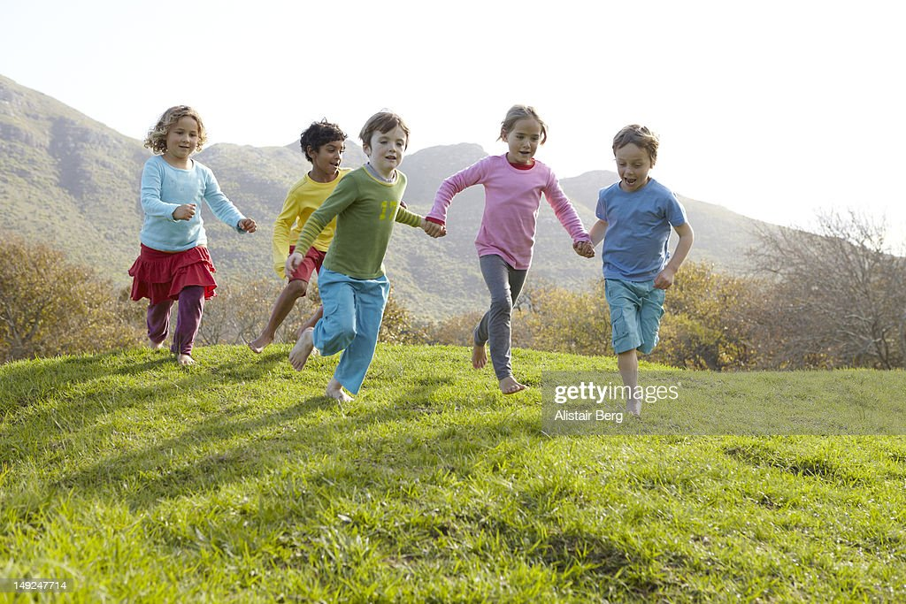 Group of children running together : Stock Photo