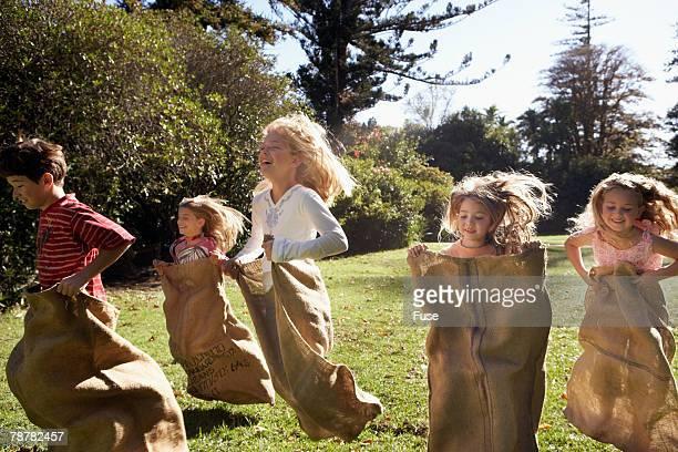 Group of Children Sack Racing in Garden