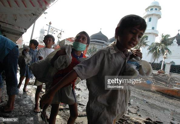 A group of children scavenges for anything still usable near the Agung mosque in the tsunamidevastated area of downtown Banda Aceh Indonesia on...