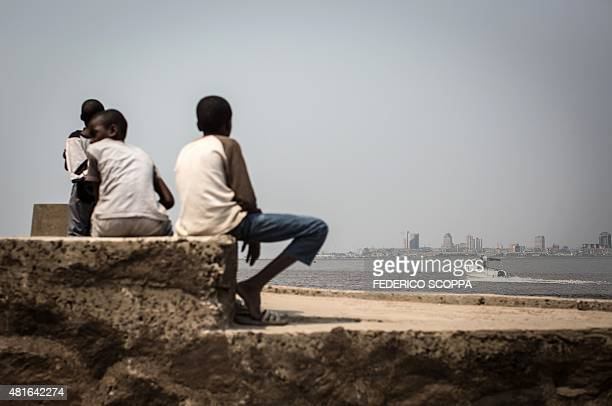 A group of children sit on the shores of the Congo river in Brazzaville on July 22 whereas on the other side of the river the capital of the...
