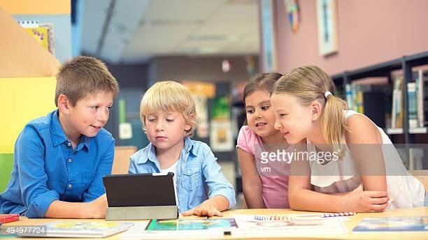 Grupo de crianças sentado à volta de tablet digital na biblioteca