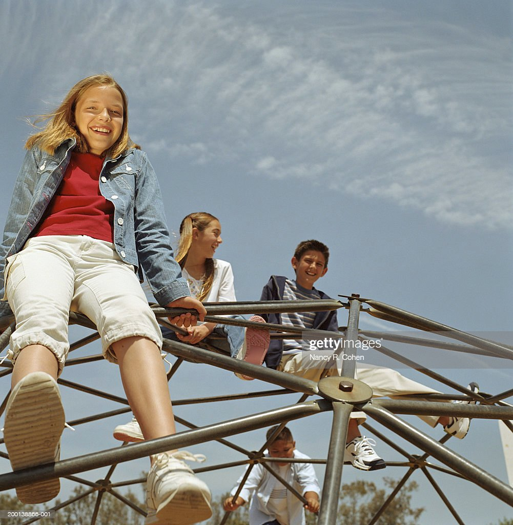 Group of children (10-12) sitting atop jungle gym, low angle view : Stock Photo