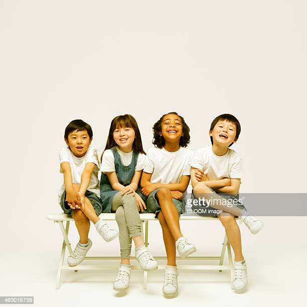 Group Of Children Sitting On A Bench