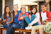 Group Of Children Sitting On Bench In Mall Smiling To Camera
