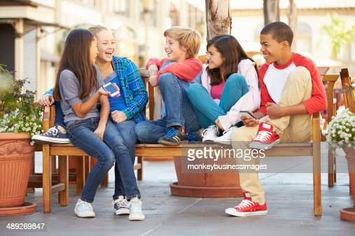 Group Of Children Sitting On Bench In Mall : Stock Photo