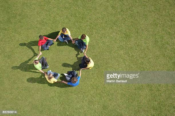 Group of children sitting on grass in circle formation
