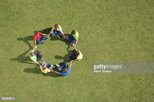 Gruppe von Kindern sitzen auf Gras im Kreis formation