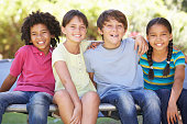 Group Of Children Sitting On Edge Of Trampoline Together Smiling To Camera.