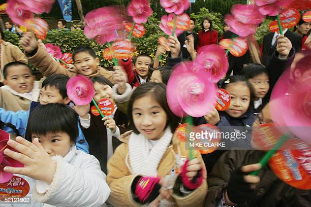 A group of children spin colored wheels during early celebrations for Chinese New Year at an amusement park in Hong Kong 02 February 2005 This Lunar...