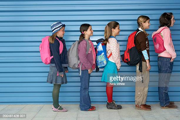 Group of children (8-11) standing by blue wall, side view