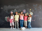 Group of children (7-9 years) standing in front of chalkboard, portrait