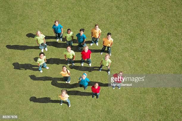 Gruppe von Kinder stehen im Gras Blick nach oben