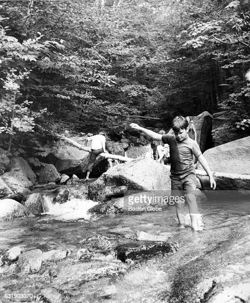 A group of children wade in the water at the Flume Gorge a natural gorge extending 800 feet at the base of Mount Liberty in Franconia Notch State...