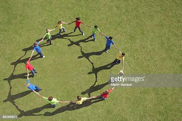 Gruppe von Kindern im Kreis holding Hände zu Fuß