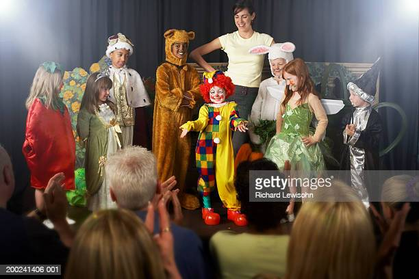 Group of children (4-9) wearing costumes and teacher on stage