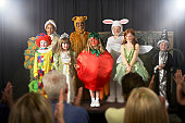 Group of children (11-14) wearing costumes on stage, portrait