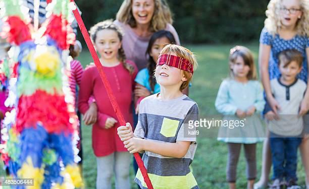 Groupe d'enfants avec garçon frapper pinata