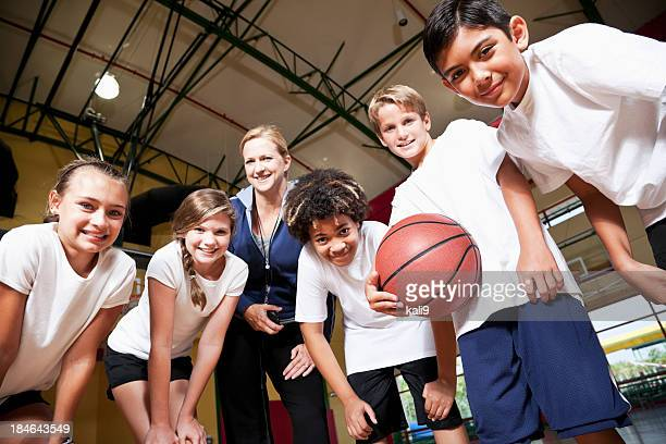 Group of children with coach playing basketball