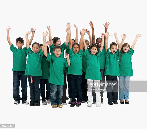 Group of children with their arms raised