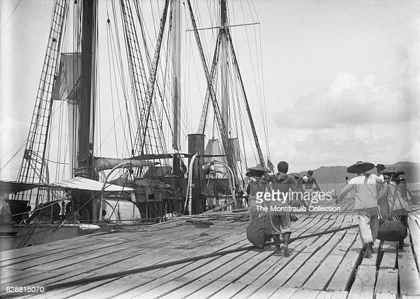 A group of chinese convicts load sacks of coal on to the Royal Naval ship HMS Waterwitch anchored off Labuan Asian coast built in 1878 as a private...